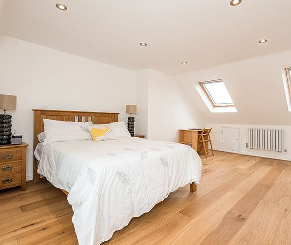 loft conversion bedroom with wood furniture and white duvet